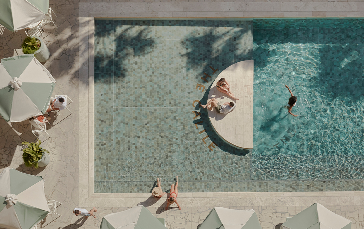 a top down view of a pool with a half moon concrete platform in the middle, and green striped umbrellas around