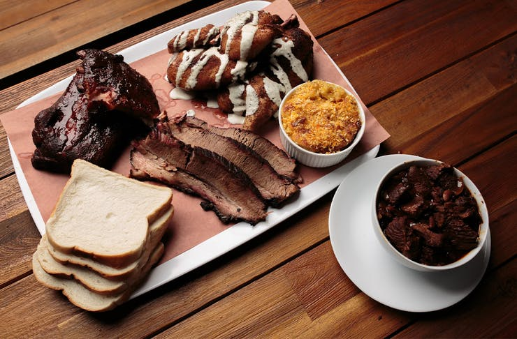 a meal of slow cooked meats and sides on a metal tray