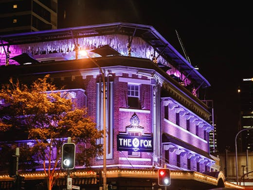 Facade of The Fox Hotel lit up with purple lights