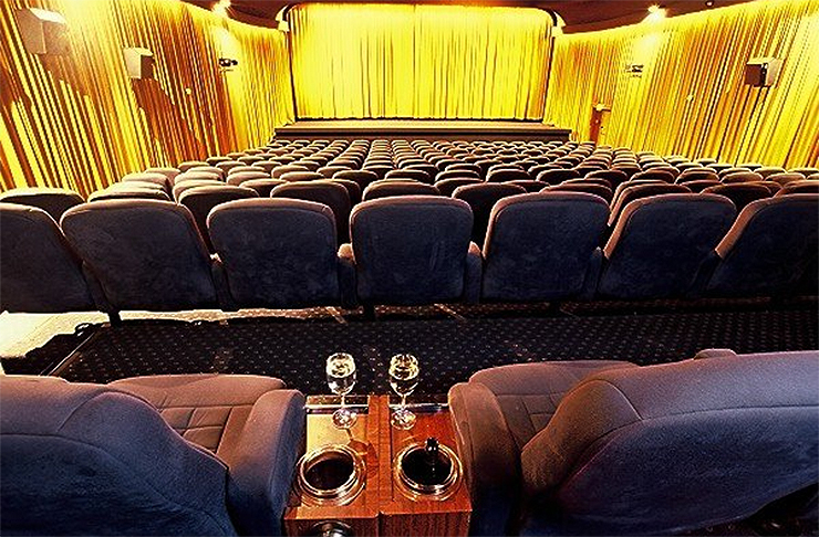 A luxurious theatre which includes seats with wine holders