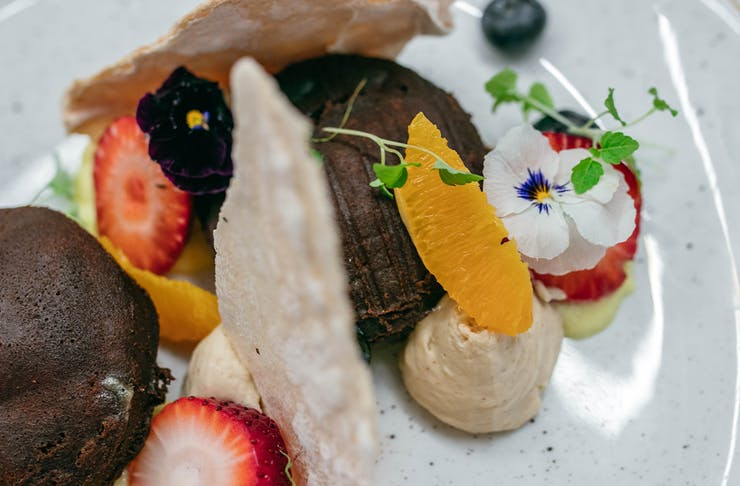 close up of a brown pancake with meringue shards, fruit and cream