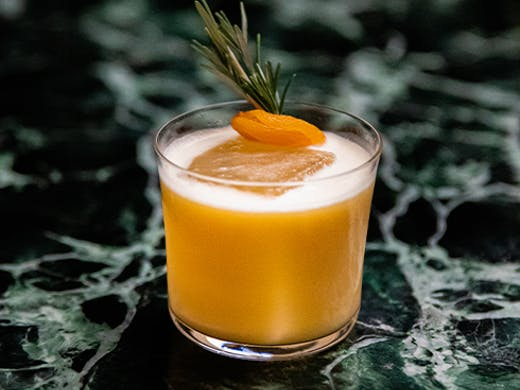 a cocktail with an apricot and rosemary on top