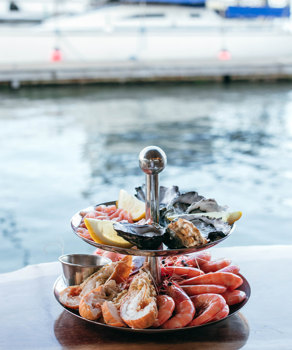 a platter of seafood in front of water