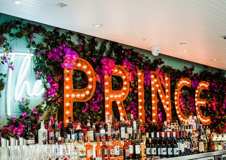 flower wall with 'prince' in neons behind a bar