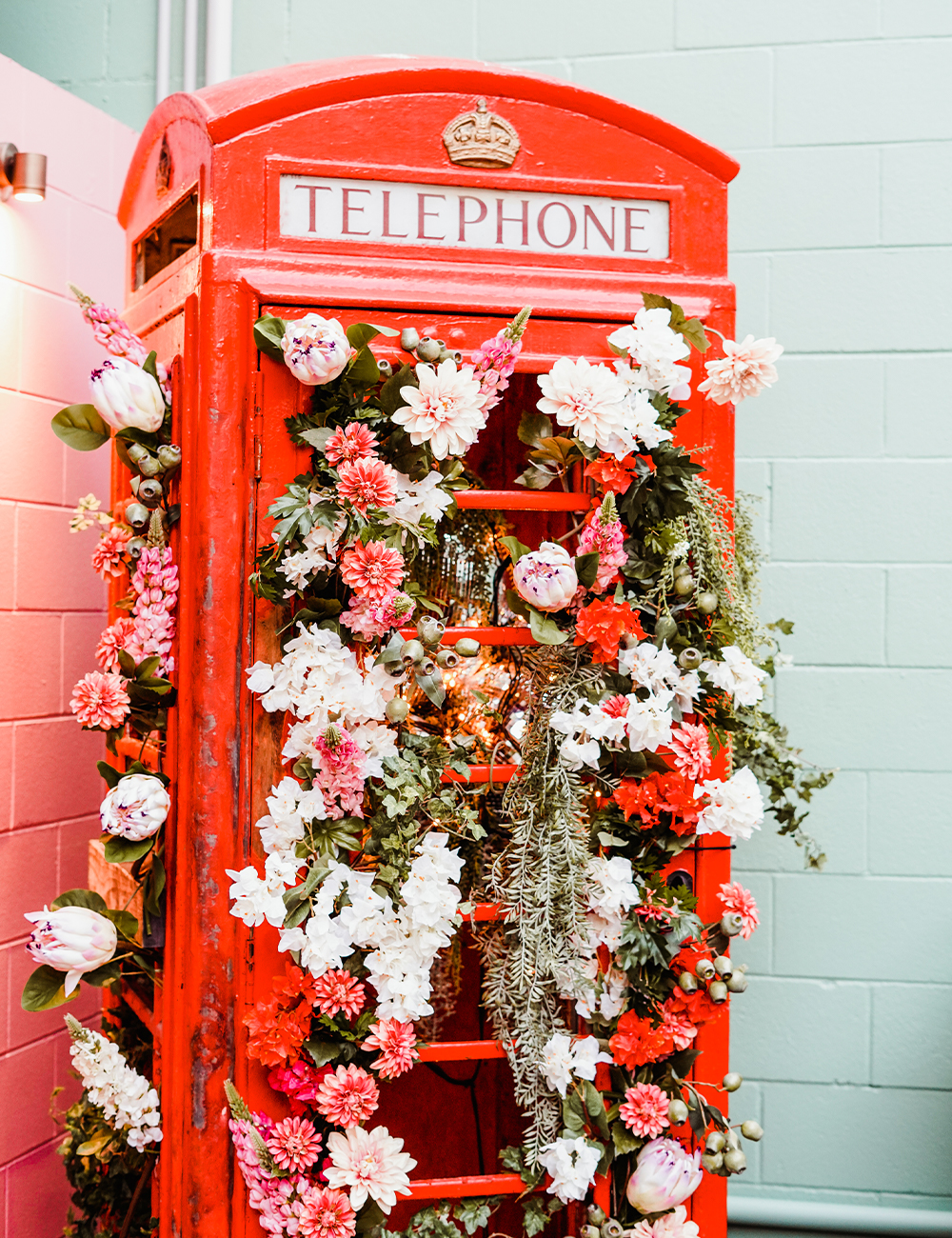 a red london style phone booth filled with flowers