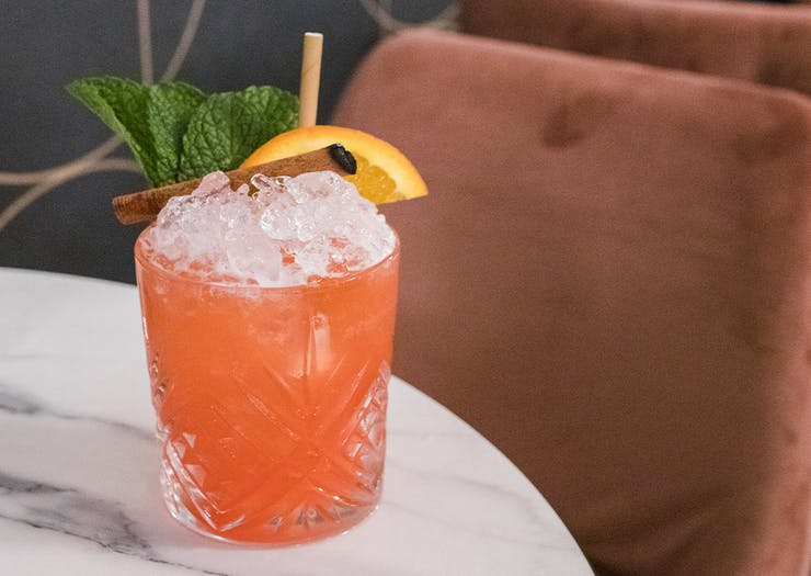 a peach coloured cocktail filled with ice