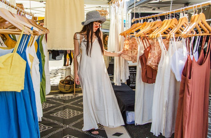 A woman dressed in a white maxi dress looks at racks of clothing at The Village Markets on the Gold Coast.