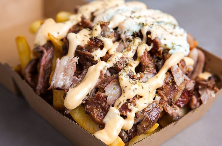 A box of fries topped with slow cooked meat and sauce