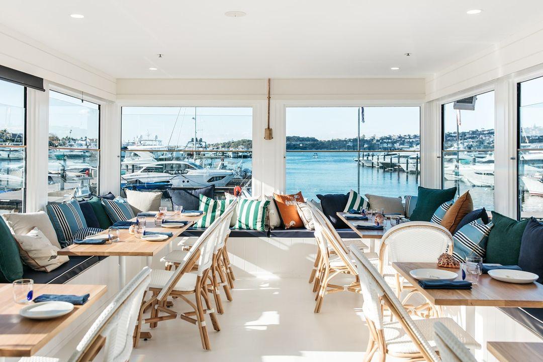 the interior of a beautiful restaurant overlooking a marina