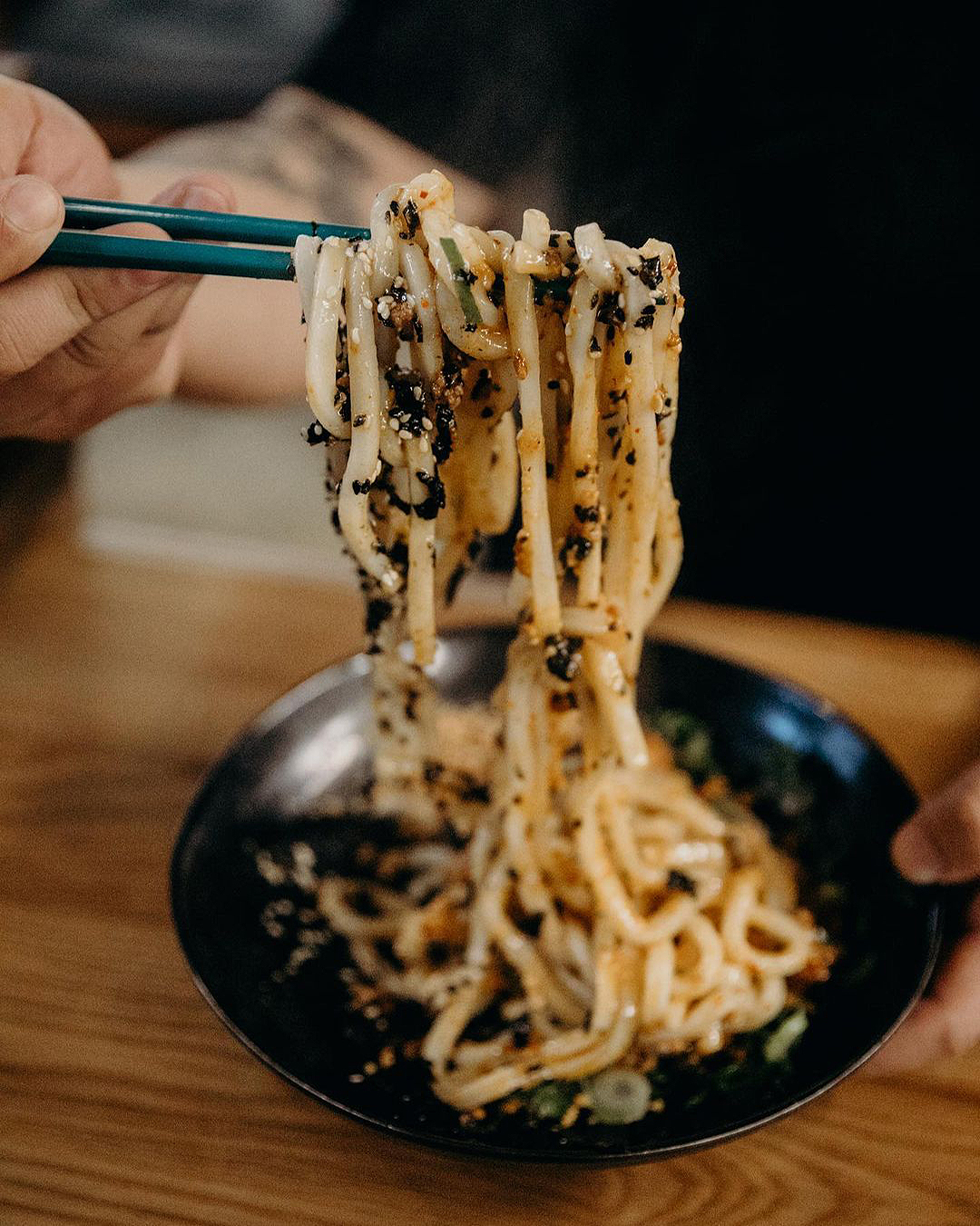 A noodle dish looks incredibly moreish held between chopsticks.