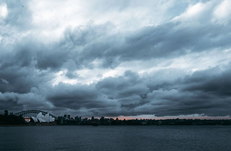 A storm over Sydney Harbour, with rain clouds hovering above the Opera House and Harbour Bridge and the sun setting.