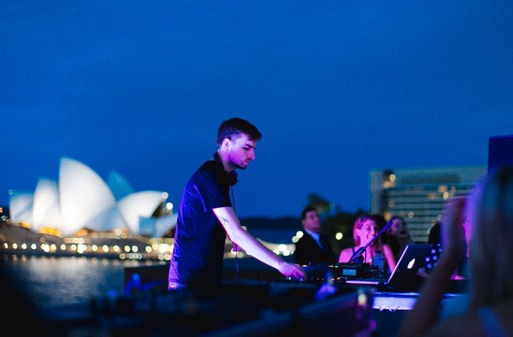 A DJ plays with the Sydney Opera House in the background.