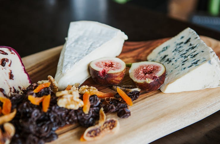 cheese on a board with dried fruits
