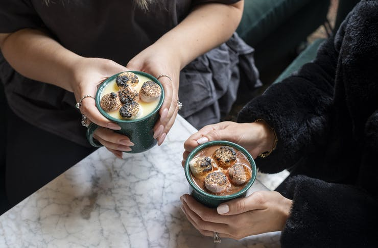 two people holding mugs of hot chocolate