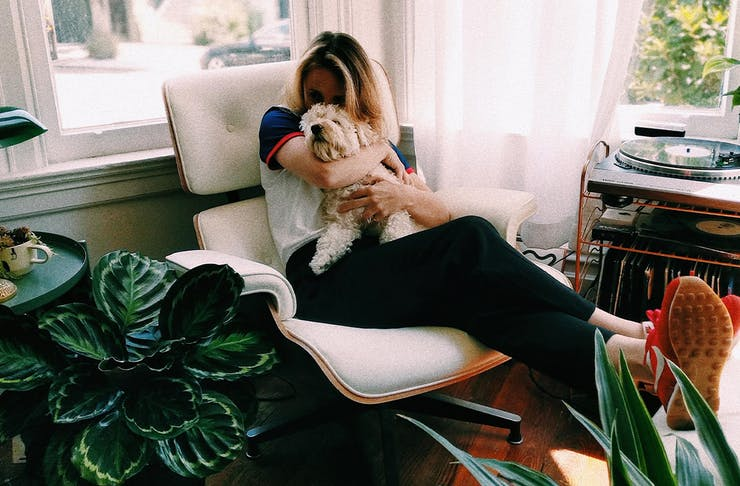 woman cuddling a puppy sitting on a lounge chair in her living room