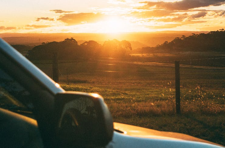 A car is pulled over to watch the sun set over farmland.