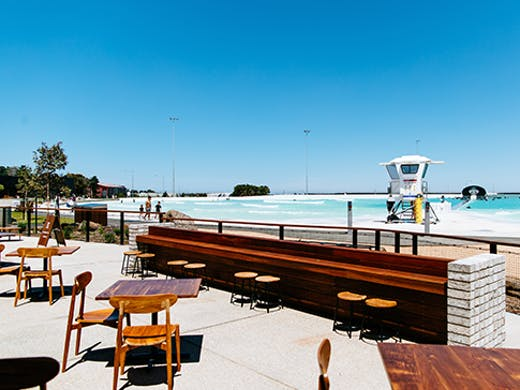 A restaurant next to a large surf park on a sunny day.