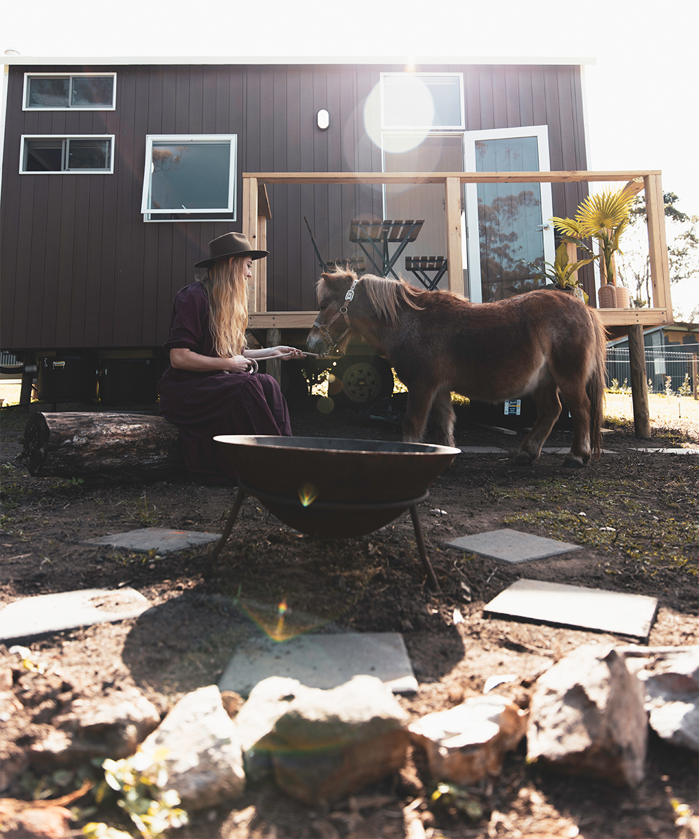 exterior of a black tiny house with a woman patting a shetland pony