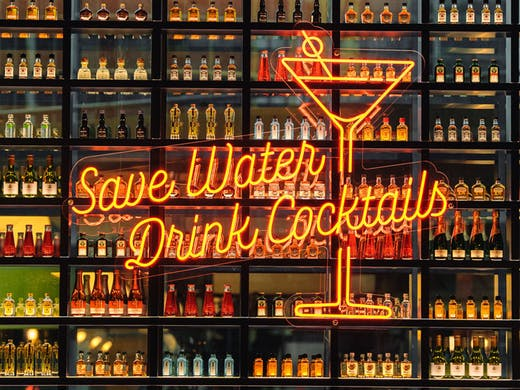 A wall of bottle cocktails with a neon sign