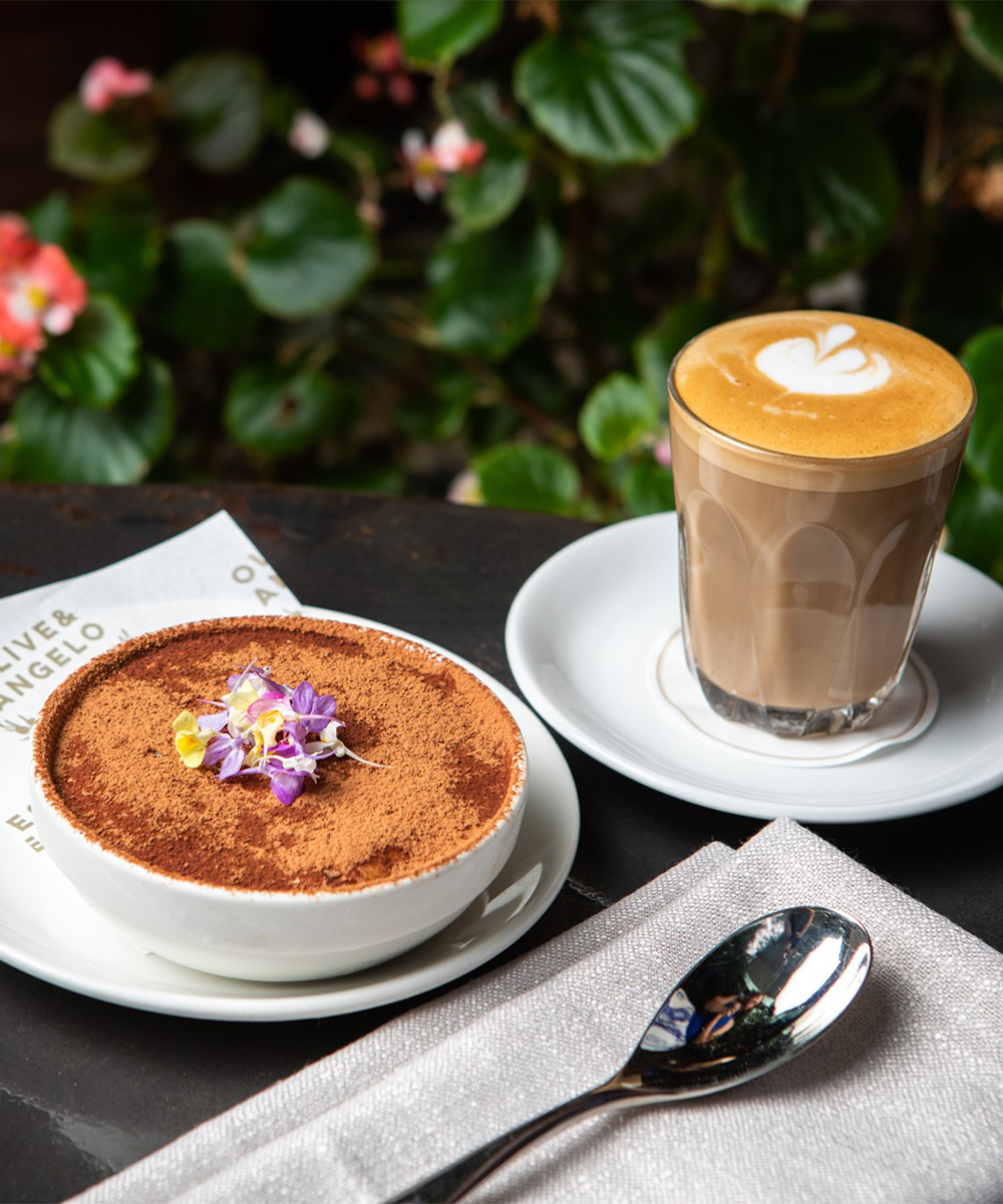 a small bowl of tiramisu topped with cocoa powder and a coffee