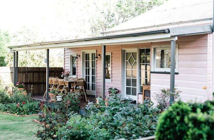 A pink cottage wth a garden and verandah