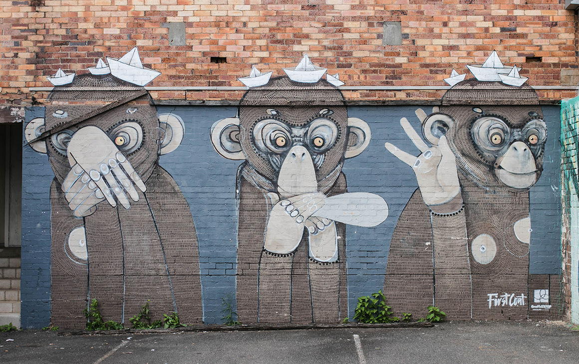 A wall painted with three monkeys in an alleyway