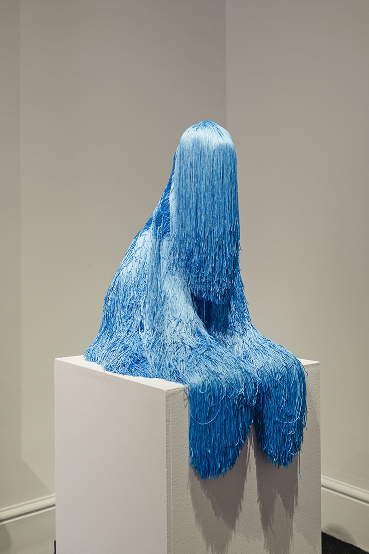 A sculpture of a person sitting on a cube covered in blue tinsel.