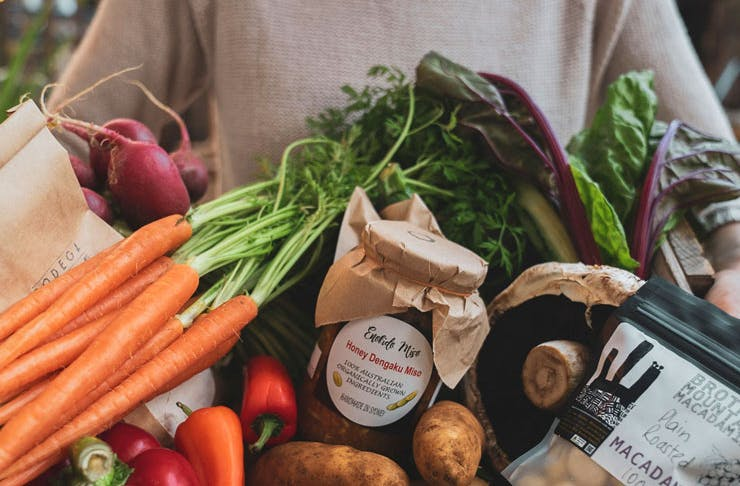A box of fruit and vegetables, featuring carrots, potatoes, radish and beetroot, as well as some condiments.