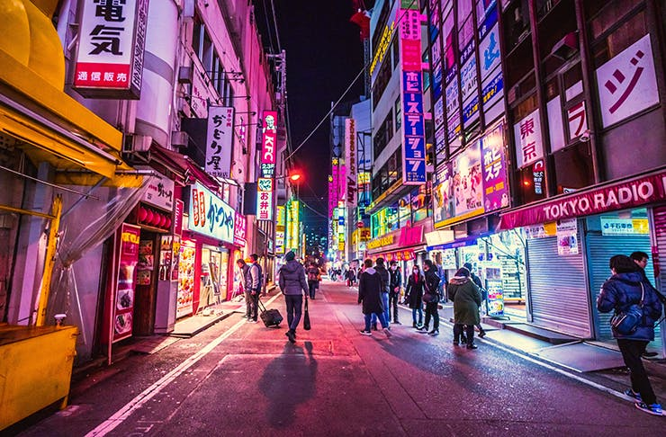 Neon-lit Tokyo street at night from the best travel shows you can stream