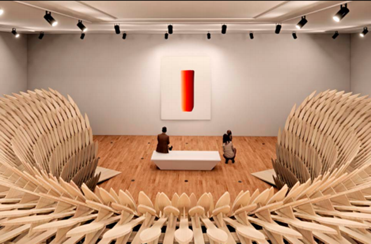 A large wooden circular installation in an art gallery. Downlights flood the room with brightness.