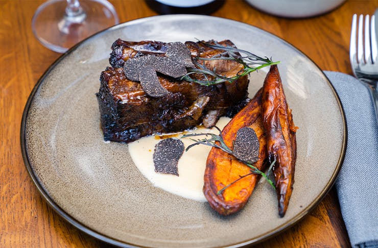 a beef short rib on a plate topped with truffle shavings