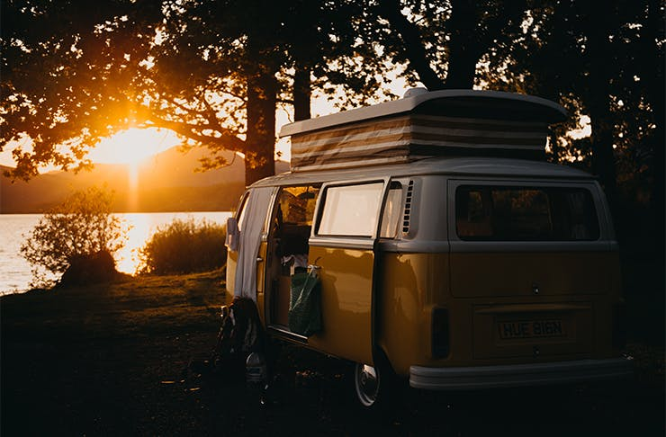 A photo of a caravan against the backdrop of a lake and the setting sun.