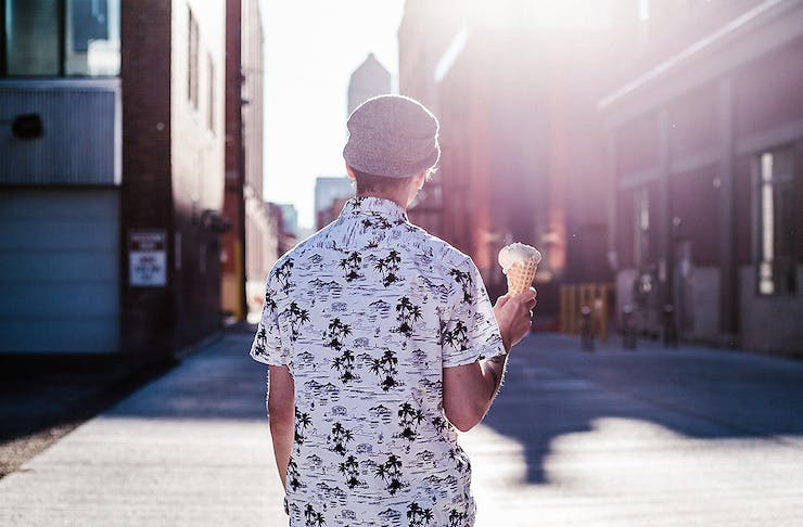 A boy walking in the sun with ice cream