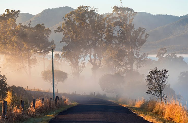 A landscape shot of an empty road leading to a foggy valley.