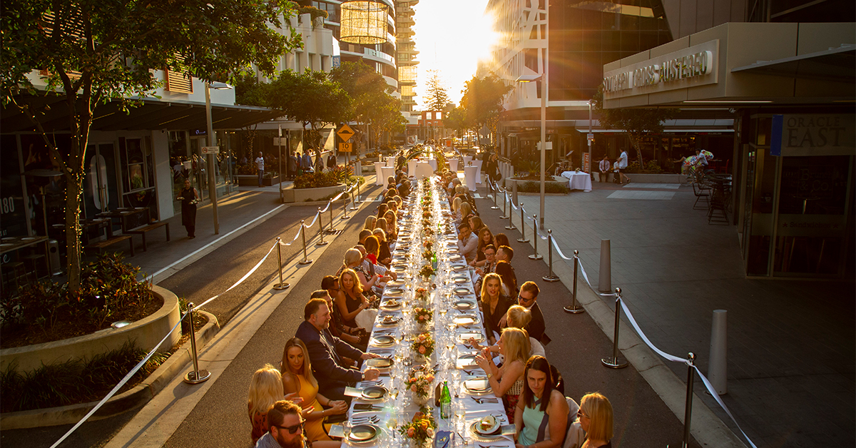 people sitting at a long dining table in the middle of broadbeach