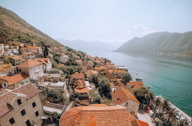 an aerial shot of a mountainous cliffside dotted with medieval-style houses overlooking a beautiful turquoise bay