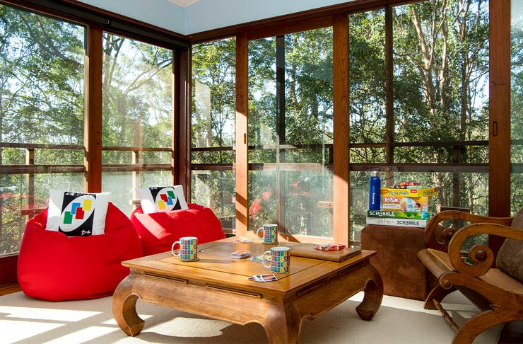 two red bean bags with uno cushions in front of floor to ceiling windows with rainforest views