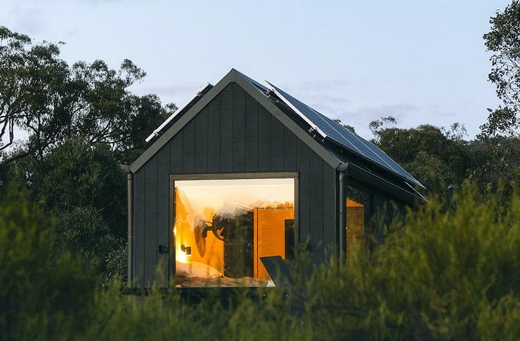 Unyoked's Louka cabin set amongst bushes and pine trees in the Central Gippsland mountains.