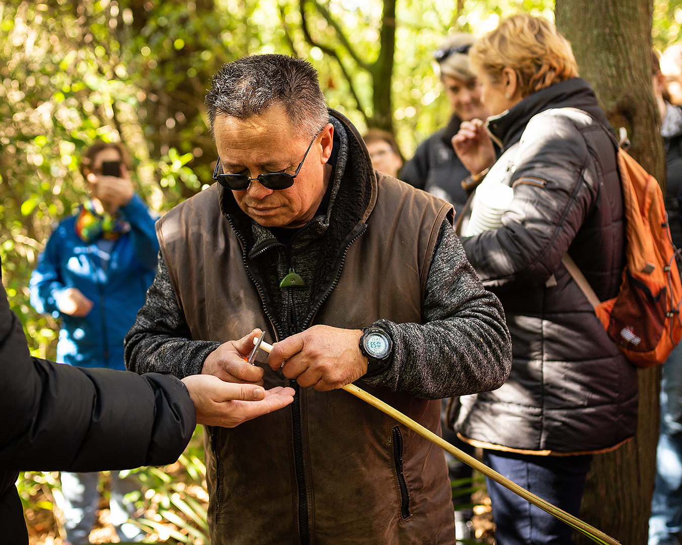 A man teaches foraging in the forest.