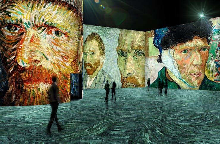 People walking through a giant digital art gallery featuring works from Van Gogh.
