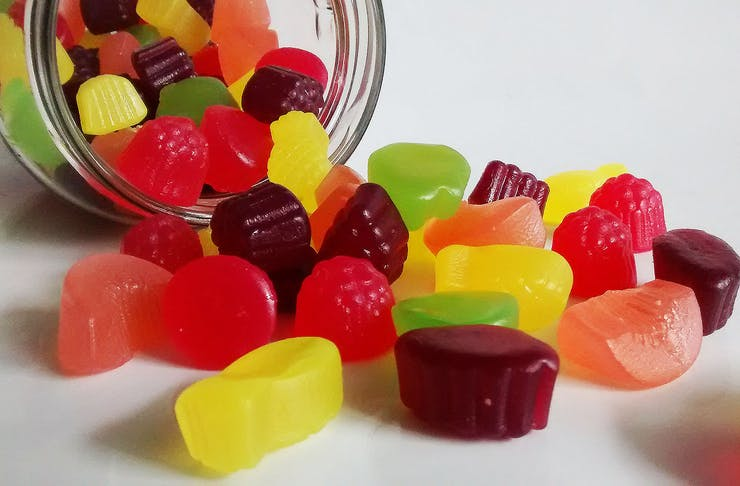 A glass jar spills multi-coloured confectionary out onto a white table.