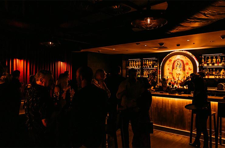 A crowd of people drinking cocktails in the dark interior of Broadbeach's new hidden speakeasy.