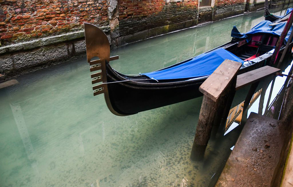 A view shows clearer waters by a gondola in a Venice canal on March 17, 2020 as a result of the stoppage of motorboat traffic, following the country's lockdown within the new coronavirus crisis.