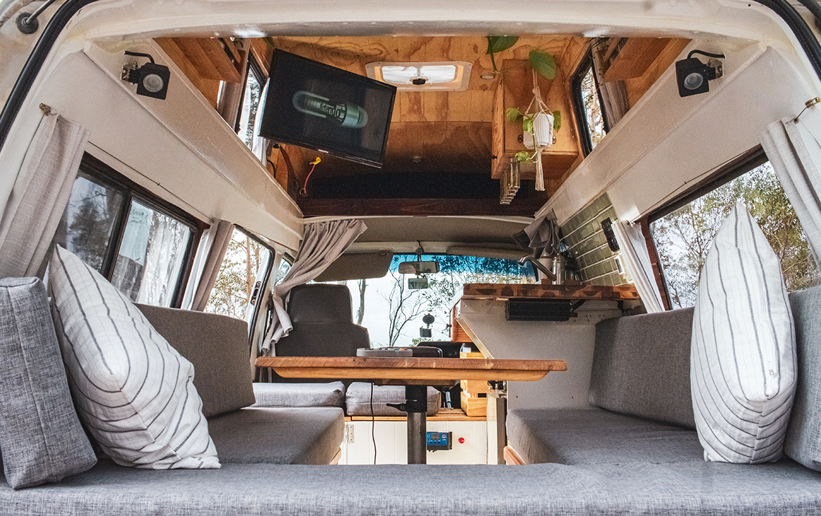 Inside of a vintage campervan with a tv, small table and kitchen