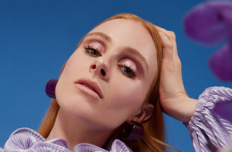 Singer-songwriter Vera Blue in a blue dress. The blue sky can be seen in the background.