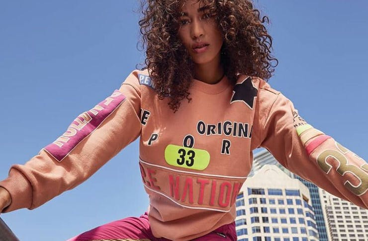 A woman wearing a pink P.E Nation jumper.