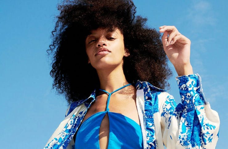 A woman wearing blue swimmers and a blue and white over shirt from Net-A-Porter with blue sky in the background.
