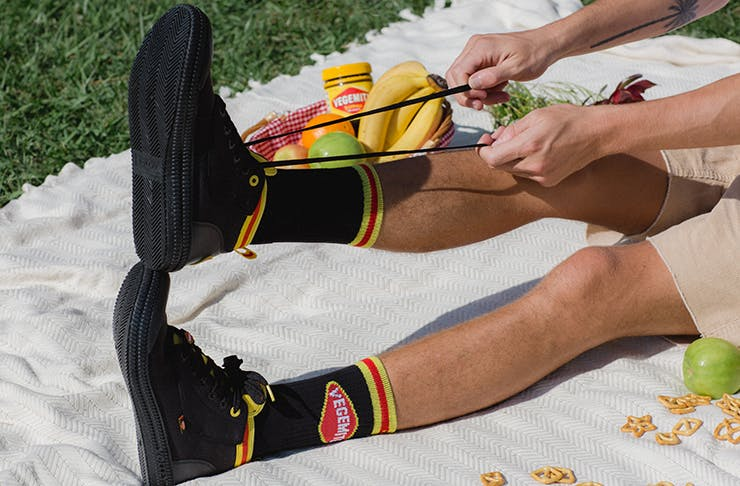 A pair of Vegemite-branded Volleys sneakers on a white picnic rug.