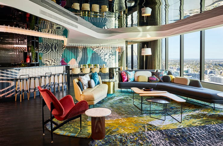 Interior of W Brisbane's Wow Suite, with floor to ceiling windows overlooking the river and luxe furnishings.