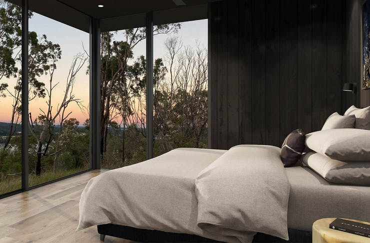 A cabin with a bed and a rainforest view.